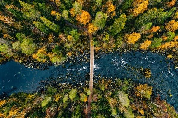 Aerial view of fast river flow through the rocks and colorful forest. Autumn in Finland - Stock Photo - Images