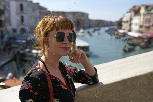 Caucasian redhead woman with floral dress looking at grand canal Venice - Stock Photo - Images