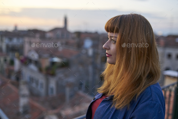 Caucasian redhead woman with denim dress overlooking rooftops in Venice - Stock Photo - Images