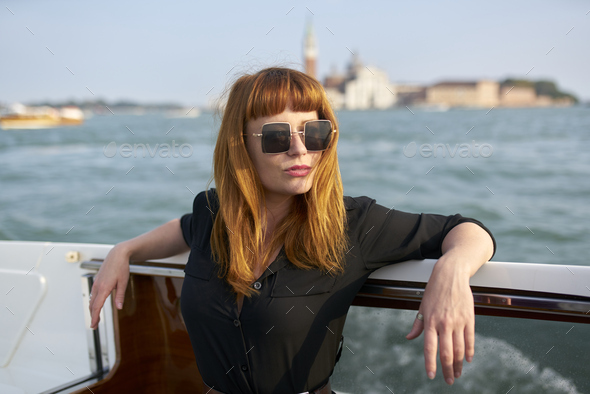 Redhead girl with long black dress, sunglasses and cowboy boots standing on yacht in Venice - Stock Photo - Images