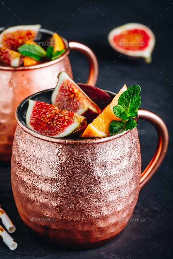 Fig moscow mule ice cold cocktail in copper cup with oranges and mint - Stock Photo - Images