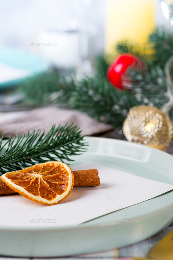 Festive Christmas and New Year details table setting with dry orange and cinnamon on a gray textile - Stock Photo - Images