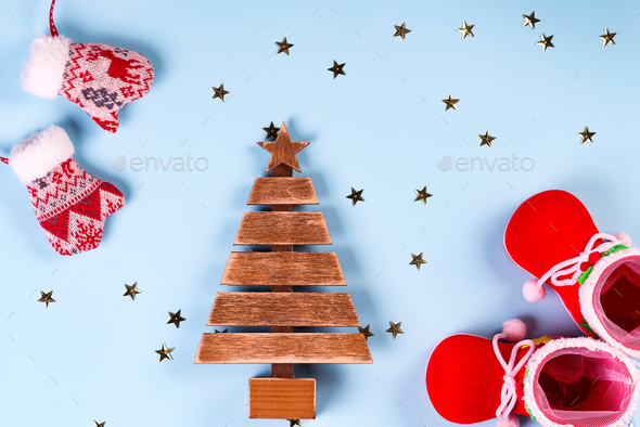santa claus clothes with shoes and mittens on a blue background, wooden fir tree with stars on the - Stock Photo - Images