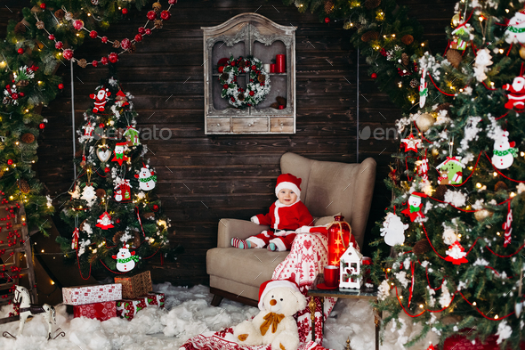 Little Santa boy in red suite sitting in big arm chair near Christmas tree - Stock Photo - Images