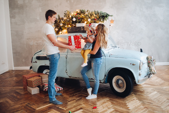 Lovely daddy giving Christmas present, big red box, for blonde mom and little cute daughter - Stock Photo - Images