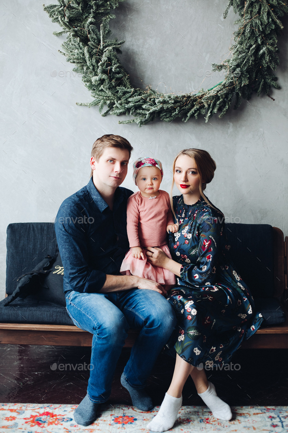 parents and daughter sitting on sofa under big fir wreath - Stock Photo - Images