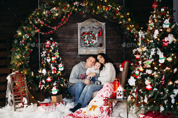 Happy family with adorable kid having fun at Christmas tree - Stock Photo - Images