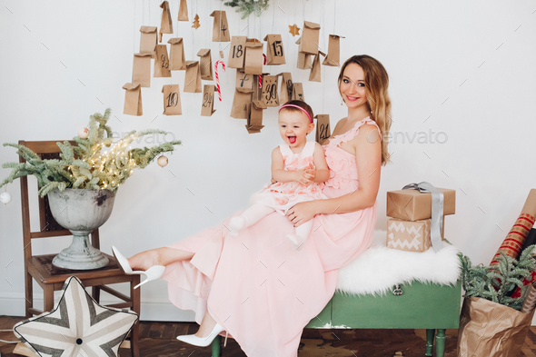 Beautiful mom with little daughter in pink dresses playing near Christmas decoration - Stock Photo - Images