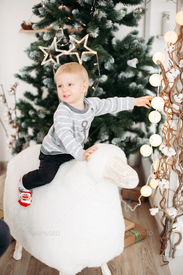 Blonde little boy in gray sweater and black jeans lying on roof among confetti - Stock Photo - Images