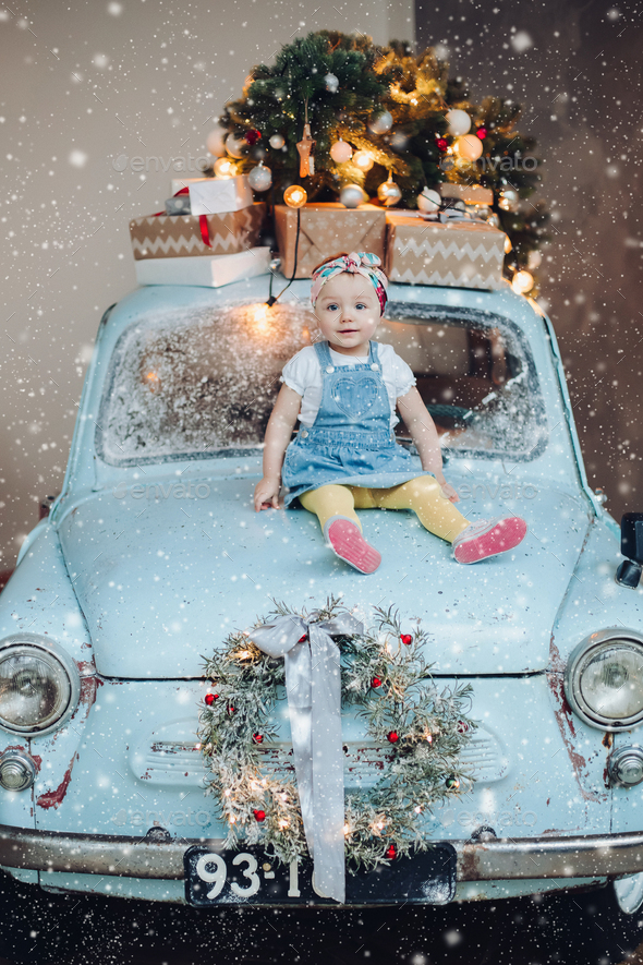 Front view of sweet and fashionable little cute girl sitting on blue retro car decorated for - Stock Photo - Images