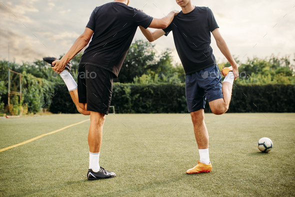 Two soccer players doing stretching exercise - Stock Photo - Images