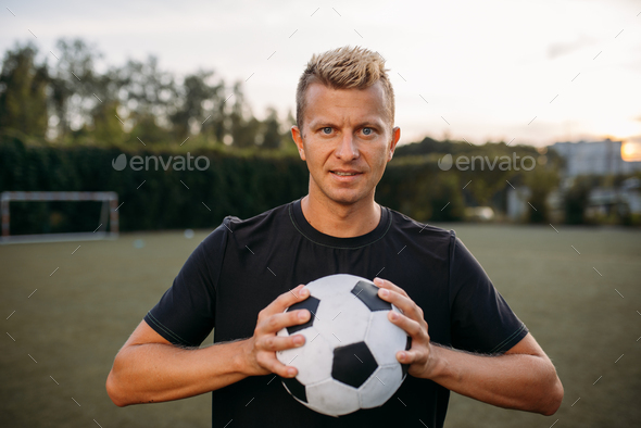 Soccer player holding ball in hands on the field - Stock Photo - Images