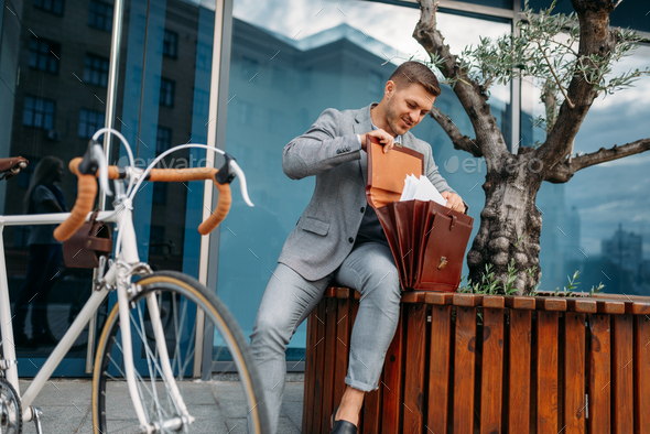 Businessman bicyclist puts document into briefcase - Stock Photo - Images