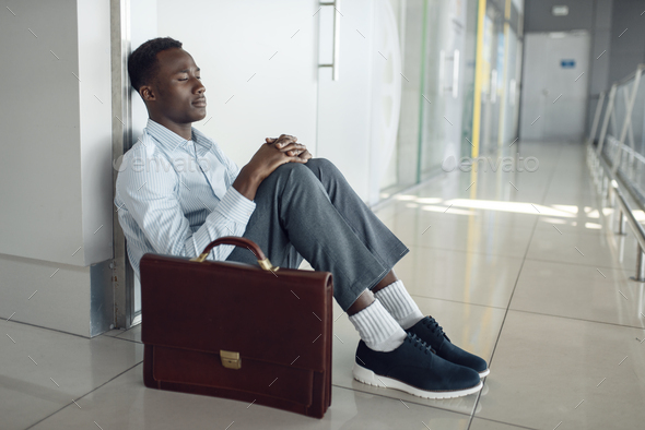 Businessman sitting on the floor in office hallway - Stock Photo - Images