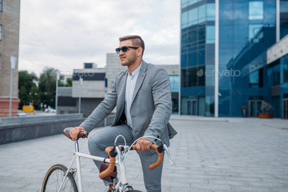 One businessman in sunglasses on bicycle, downtown - Stock Photo - Images
