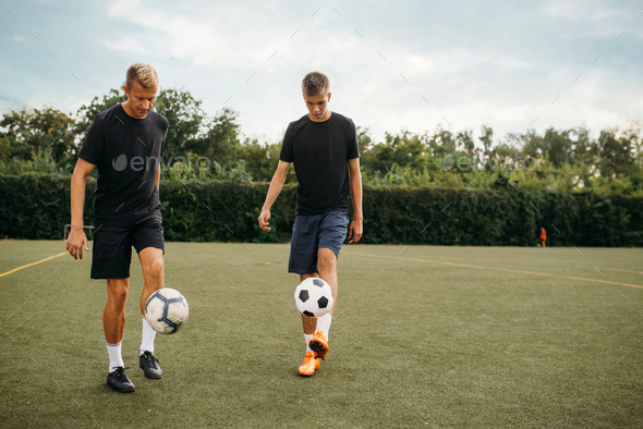 Soccer players training with balls on the field - Stock Photo - Images