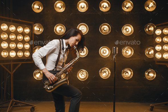 Female saxophonist plays the saxophone on stage - Stock Photo - Images