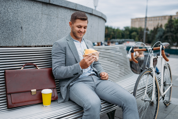Businessman with bike eats lunch on the bench - Stock Photo - Images