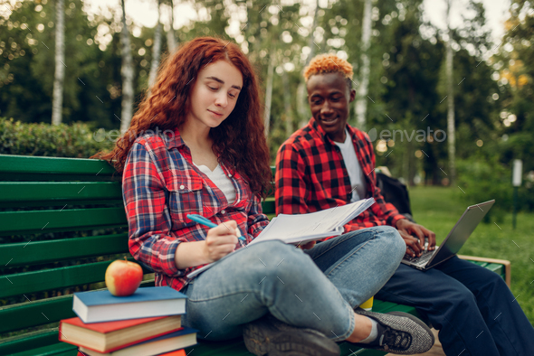 Two students drinks coffee on the bench in park - Stock Photo - Images