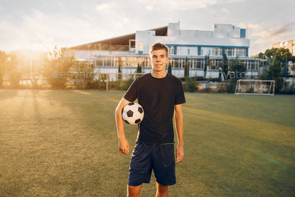 Male soccer player poses with ball in hands - Stock Photo - Images