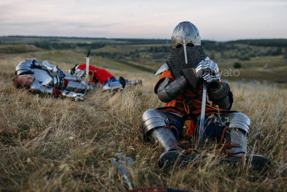 Medieval knight in armor sitting on the ground - Stock Photo - Images