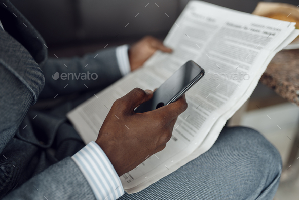 Ebony businessman hands with newspaper and phone - Stock Photo - Images
