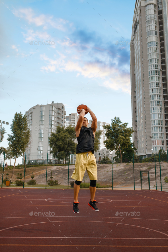 Basketball player makes a throw on outdoor court - Stock Photo - Images