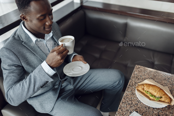 Black businessman having lunch in office cafe - Stock Photo - Images
