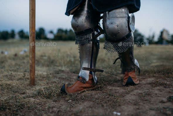 Medieval knight legs in metal armor, back view - Stock Photo - Images