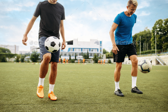 Male soccer players stuffs ball with their feet - Stock Photo - Images