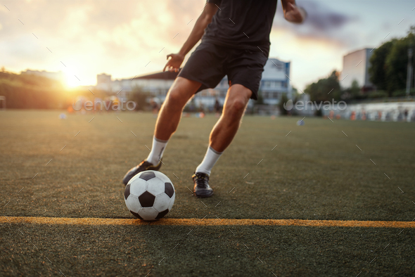 Male football player hits the ball on the field - Stock Photo - Images