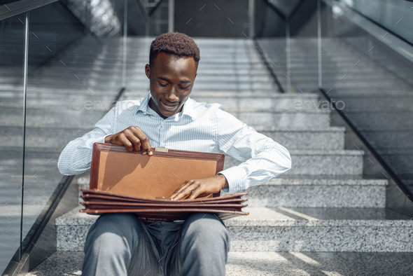 A businessman with briefcase sitting on stairs - Stock Photo - Images