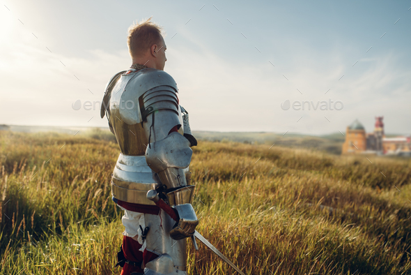 Medieval knight in armor holds sword - Stock Photo - Images