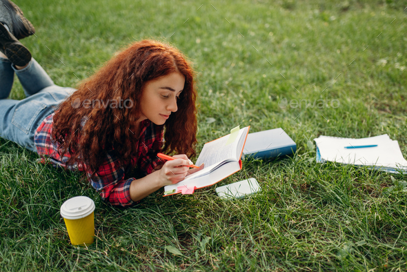 Female student preparing for exams on the grass - Stock Photo - Images