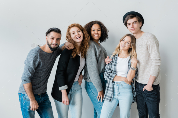 Pretty teenage girls and their boyfriends in casualwear having fun - Stock Photo - Images