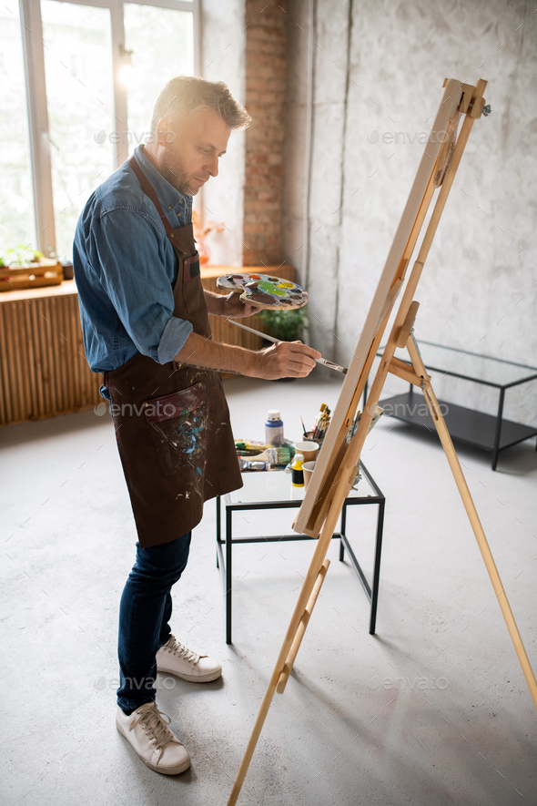 Casual man in apron standing in front of easel and painting with water colors - Stock Photo - Images