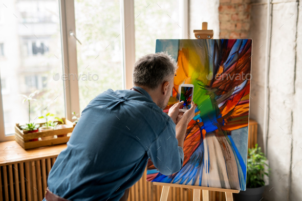 Contemporary man with smartphone taking photograph of the painting on easel - Stock Photo - Images