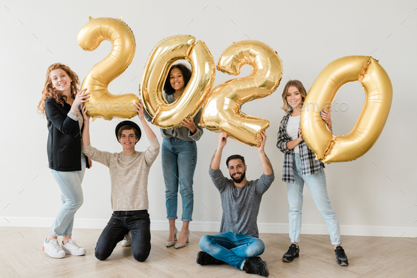 Group of five cheerful teenage friends showing number of new year - Stock Photo - Images