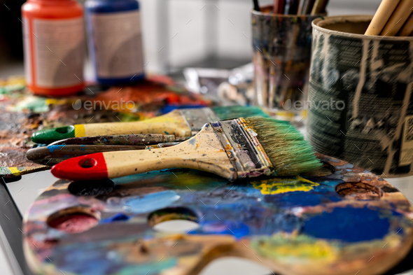 Group of paintbrushes and palettes on background of gouache jars - Stock Photo - Images