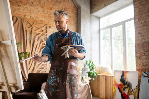 Middle aged man in apron looking at painting on easel while working in studio - Stock Photo - Images