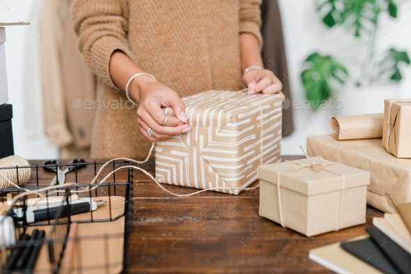 Young female binding wrapped giftbox with threads while preparing xmas presents - Stock Photo - Images
