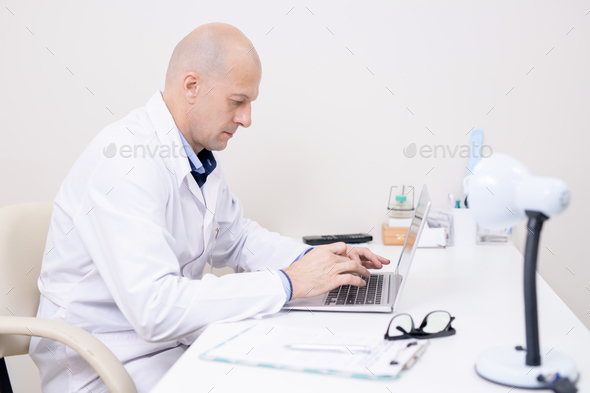 Serious middle aged doctor in whitecoat concentrating on laptop work - Stock Photo - Images