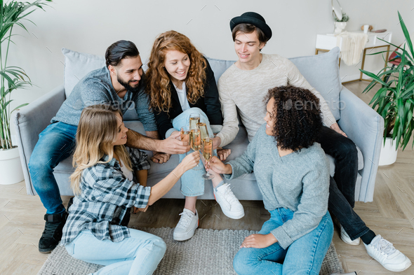 Five young cheerful friends in casualwear clinking with flutes of champagne - Stock Photo - Images