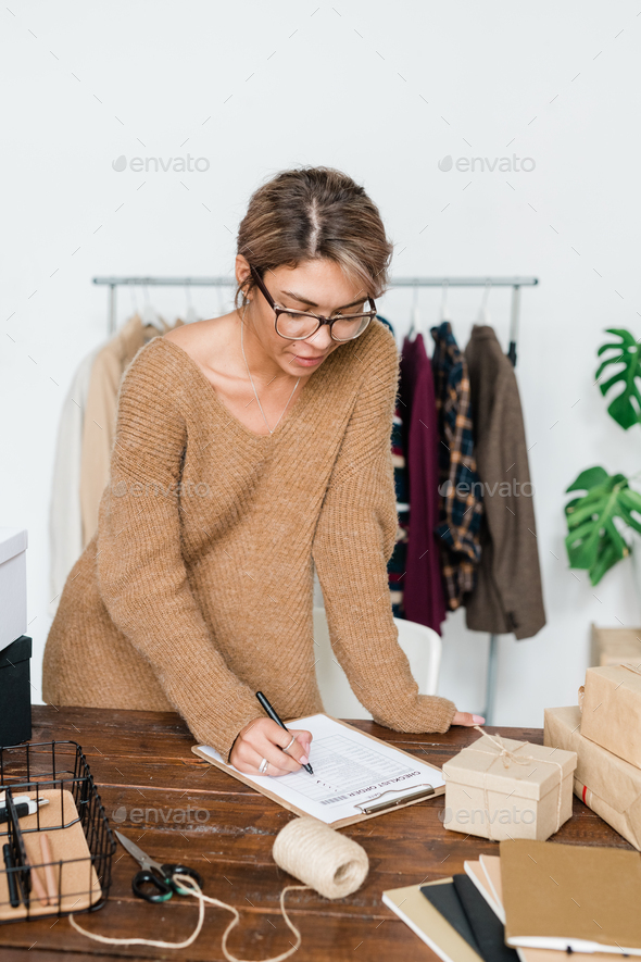 Young casual woman standing by wooden table and checking list of ordered items - Stock Photo - Images