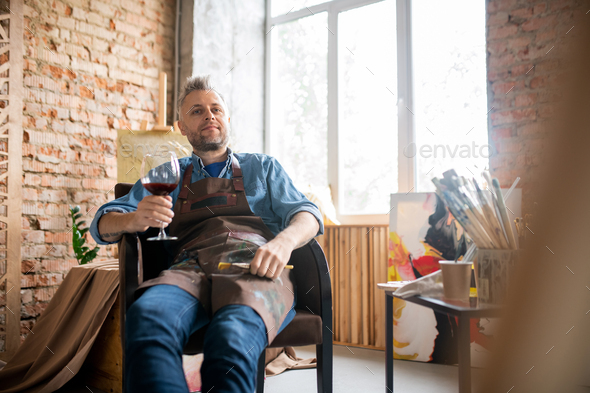 Satisfied artist in workwear having glass of red wine while enjoying break - Stock Photo - Images