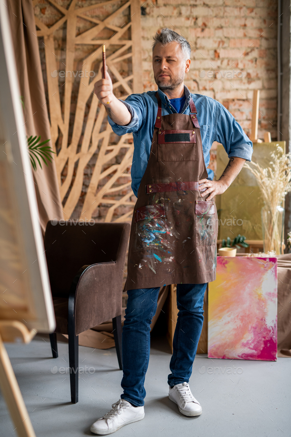 Artist with paintbrush determining center of painting or paper sheet - Stock Photo - Images