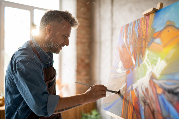 Happy mature master of arts in apron working over abstract painting - Stock Photo - Images