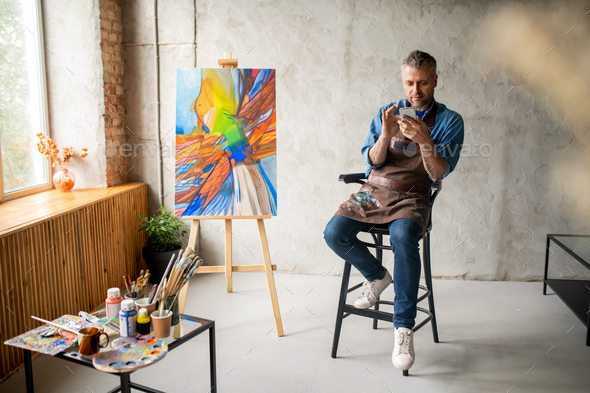 Casual painter with smartphone sitting in studio and scrolling in mobile phone - Stock Photo - Images