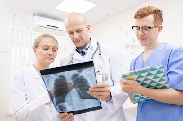 Two doctors discussing x-ray of lungs while young intern making notes - Stock Photo - Images