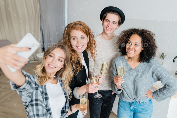 Group of happy young multicultural friends with champagne making selfie at party - Stock Photo - Images